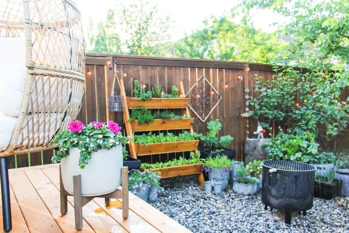 a wooden raised herb garden leans on a fence. it is surrounded by string lights, trees and more plants