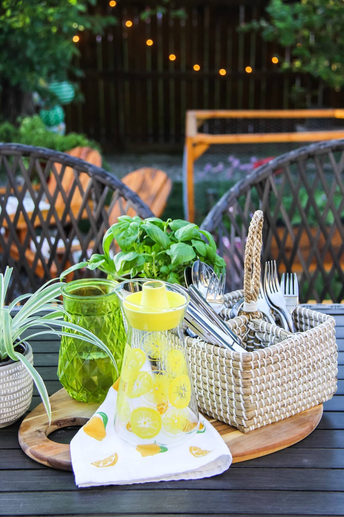 a basket of cutlery, a yellow glass jug and a basil plant sit on a table. in the background are wicker chairs and a tree and fence with a string of patio lights