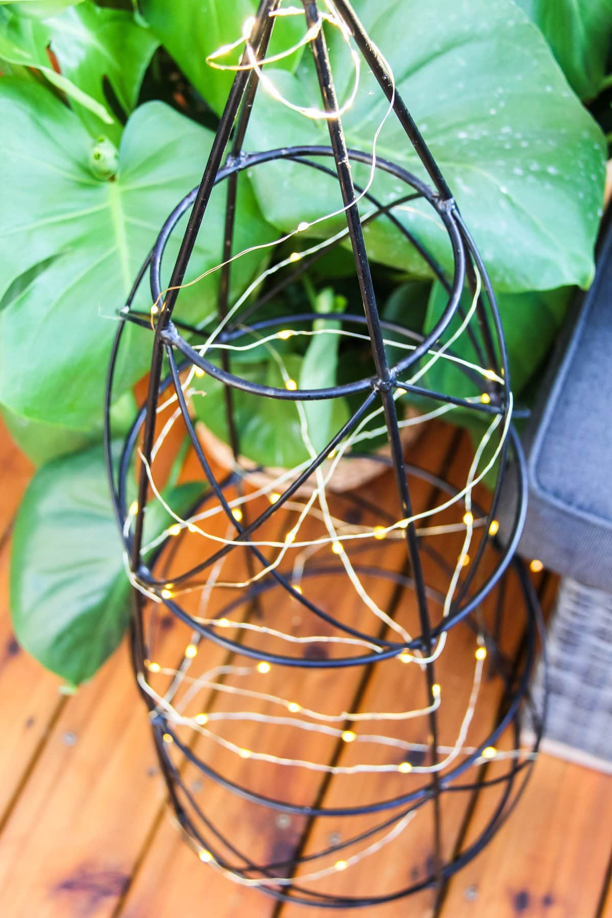 a tomato cage wrapped in a string of fairy lights
