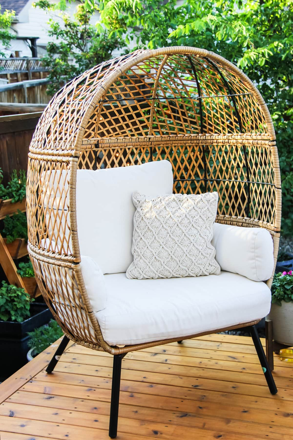 a wicker egg chair on a summer deck. in the background are trees