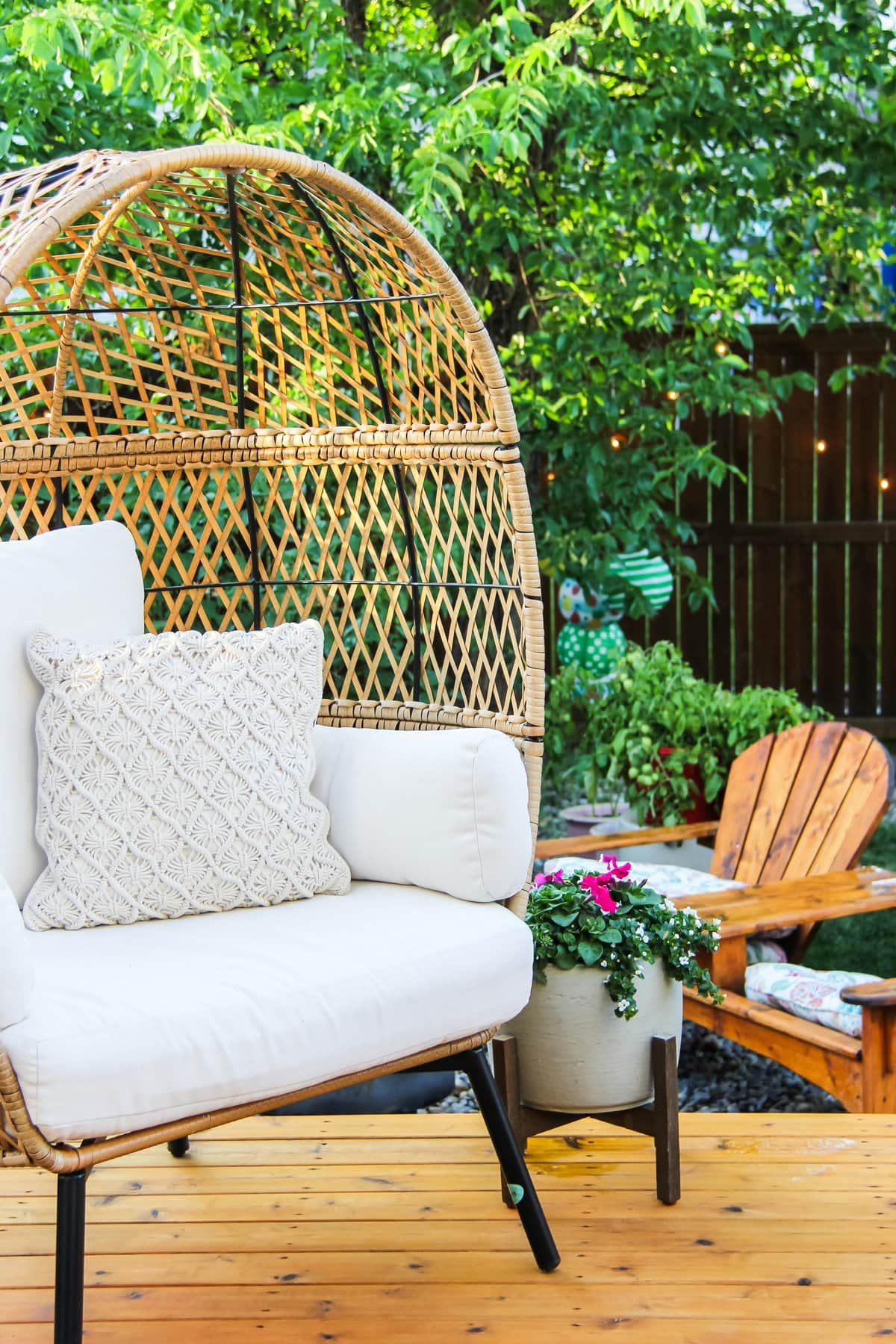 a wicker egg chair on a summer deck. in the background are trees, adirondack chairs and flowers