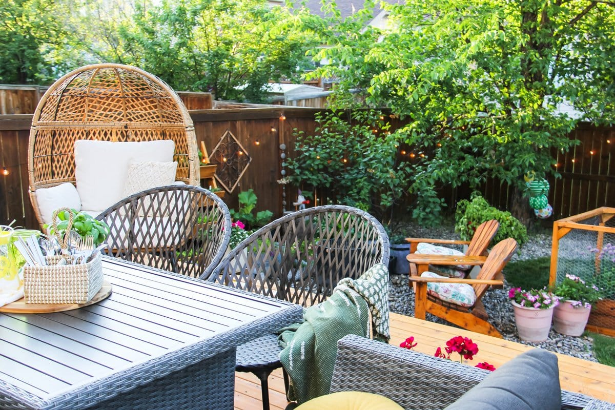 a basket of cutlery, a yellow glass jug and a basil plant sit on a table. in the background are wicker chairs and a tree and fence strung with patio lights
