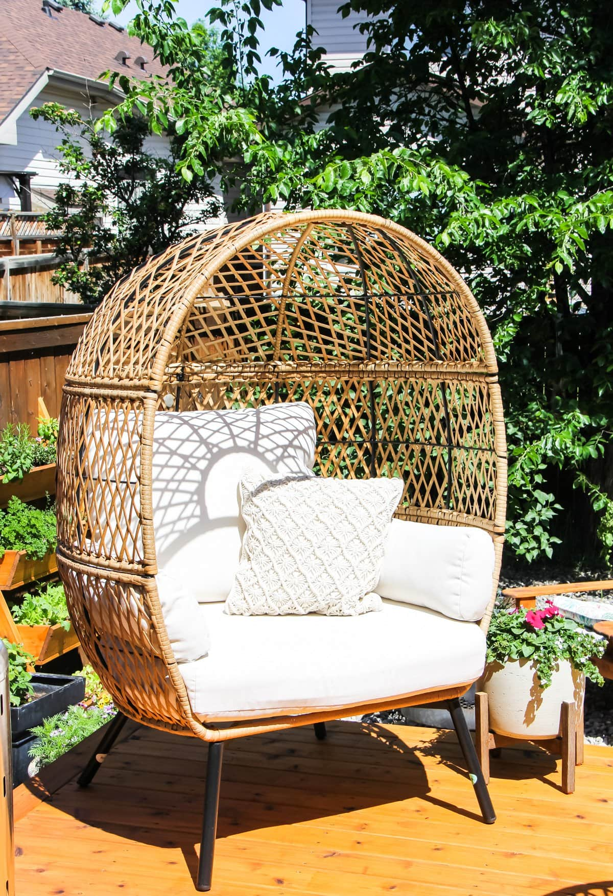a wicker egg chair on a summer deck. in the background are trees and flowers