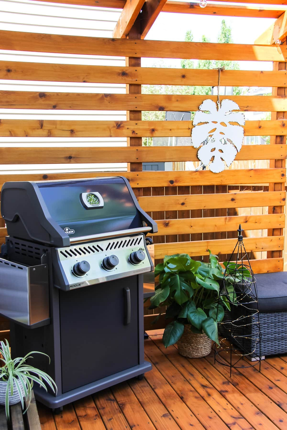 a deck with a small grey barbecue, a Monsterra plant and a white metal Monsterra wall hanging