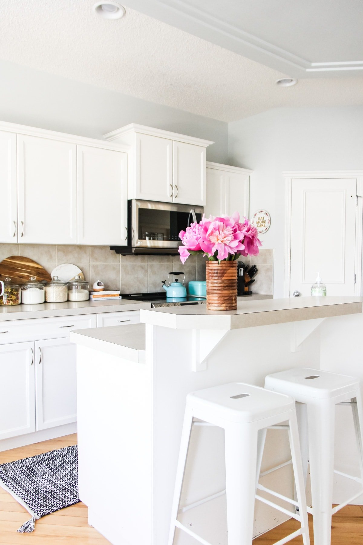 a white kitchen with white cupboards and white stools. on the counter is a wooden vase with pink peonies