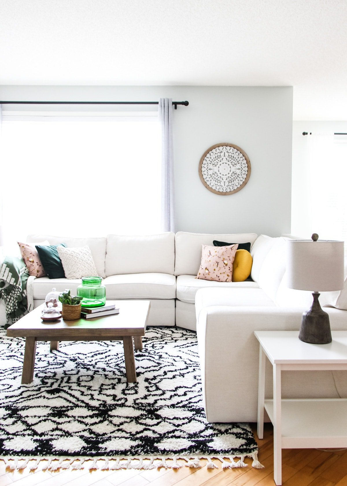a bright living room with a cream sectional couch, a wooden coffee table holding a green vase, books and a plant, a black and white rug