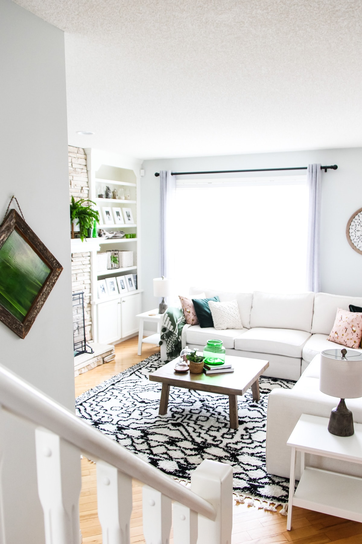 a view from a set of stairs into a bright living room with a cream sectional couch, a wooden coffee table holding a green vase, books and a plant, a black and white rug