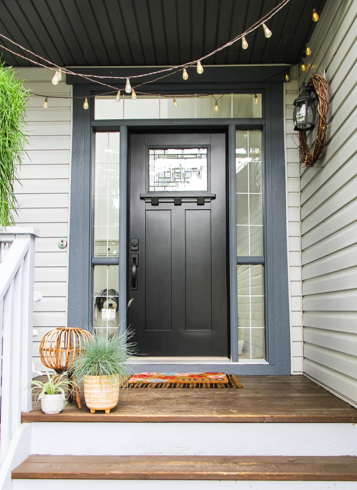 a black front door. on the porch is a flowered rug, two small planters of grass, and there are lights strung on the ceiling
