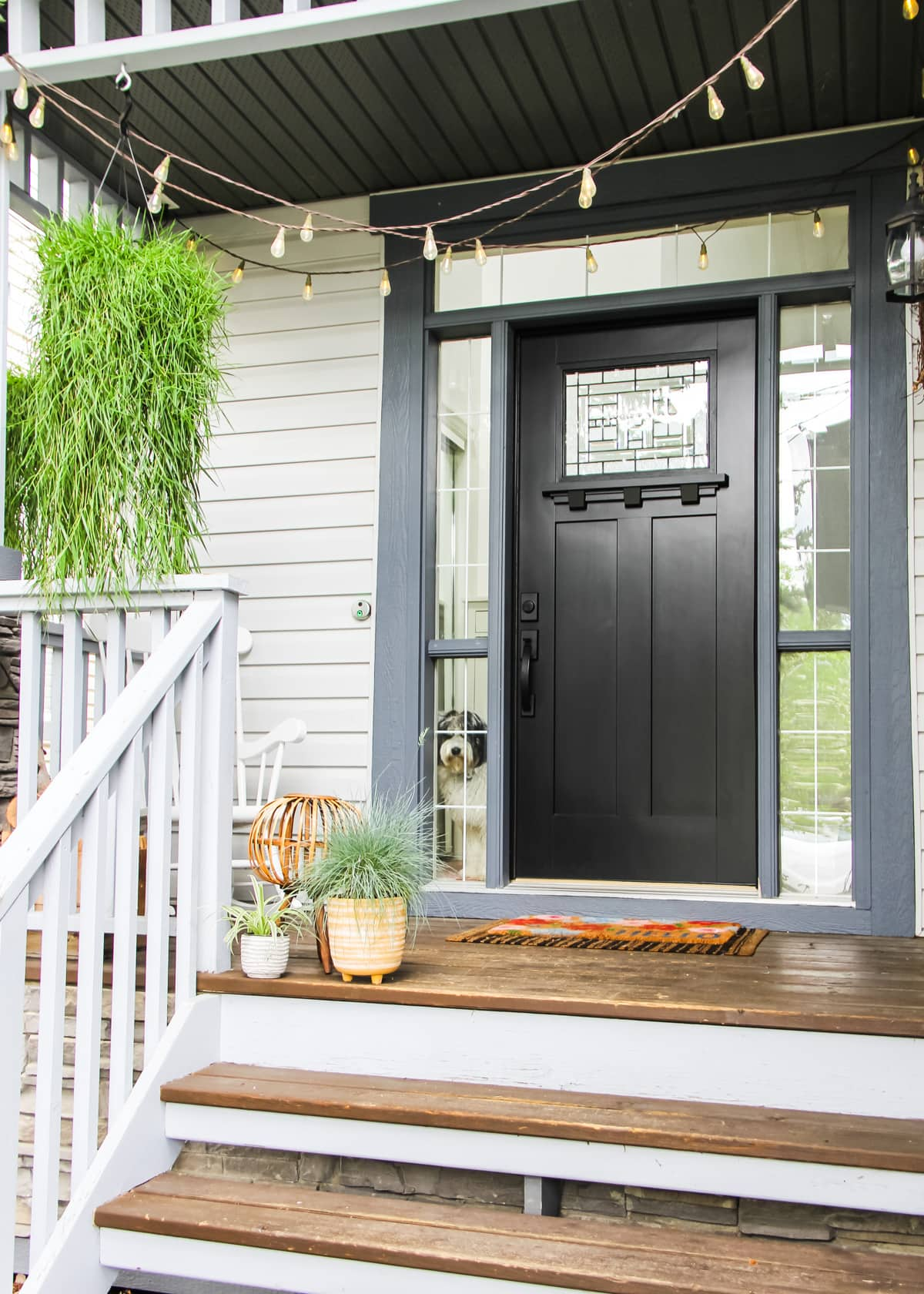 a black front door. on the porch is a hanging basket of grass, a flowered rug, two small planters of grass, and there are lights strung on the ceiling