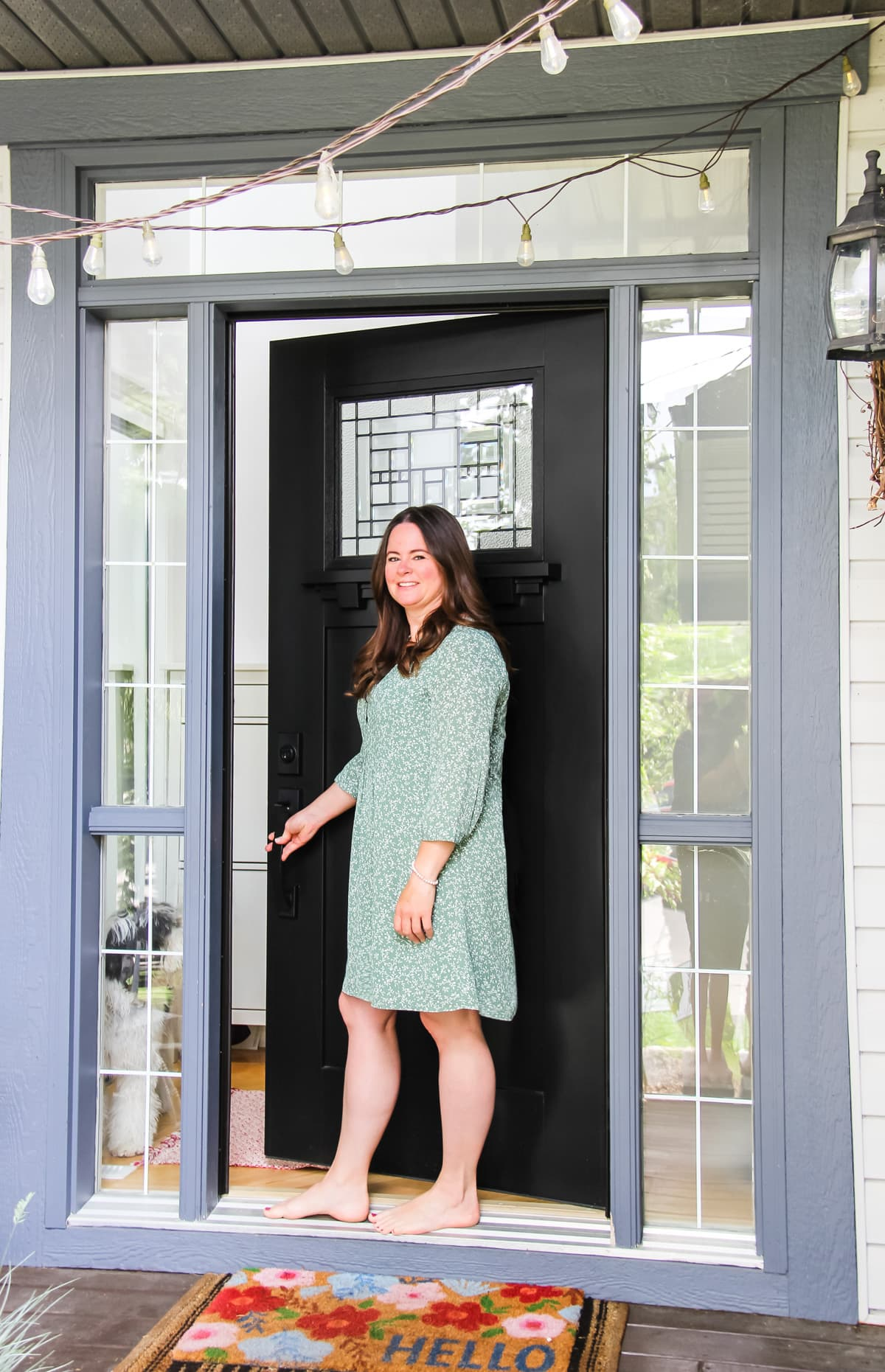 a woman in a long sleeved green flowered dress opening a black front door