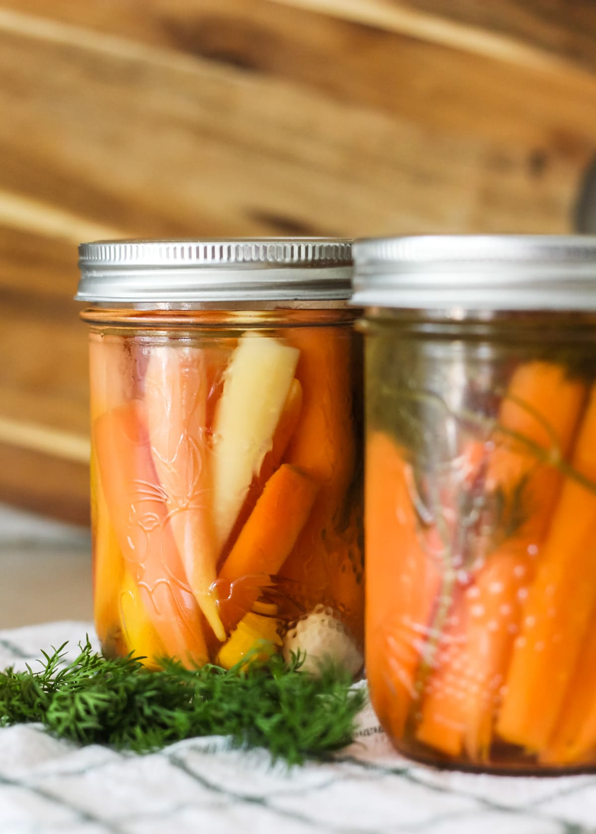 a front view of two jars of pickled carrots. the jars are sitting on a green and white checker tea towel, and are sitting next to a small bunch of fresh dill