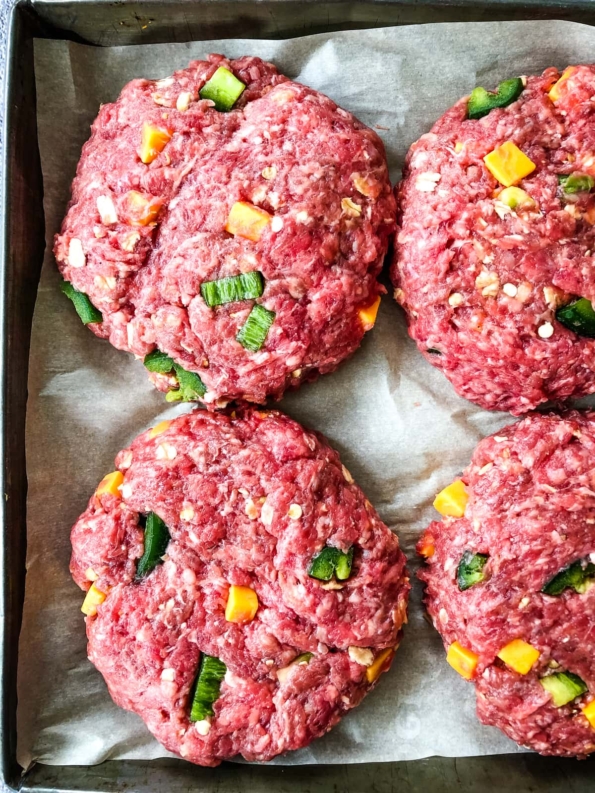 a top down view of raw Jalapeño Bacon Cheddar Burger patties