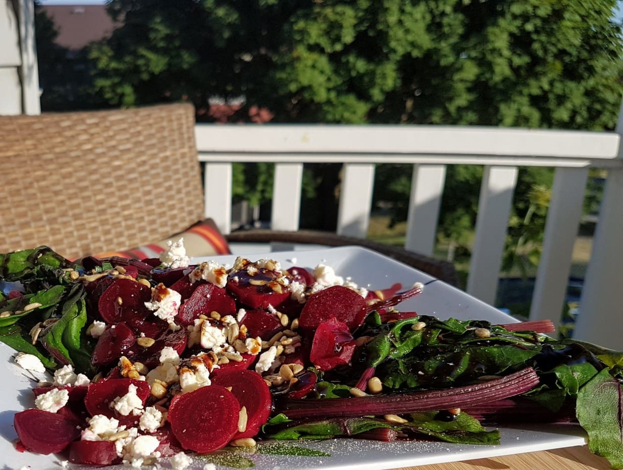 a beet salad on a white plate. in the background is a white deck railing and green trees