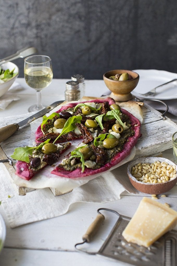 a beet pizza topped with olives and fresh greens. the pizza sits on a white wooden board on a table with wine glasses, a block of cheese, a bowl of olives and salt and pepper shakers