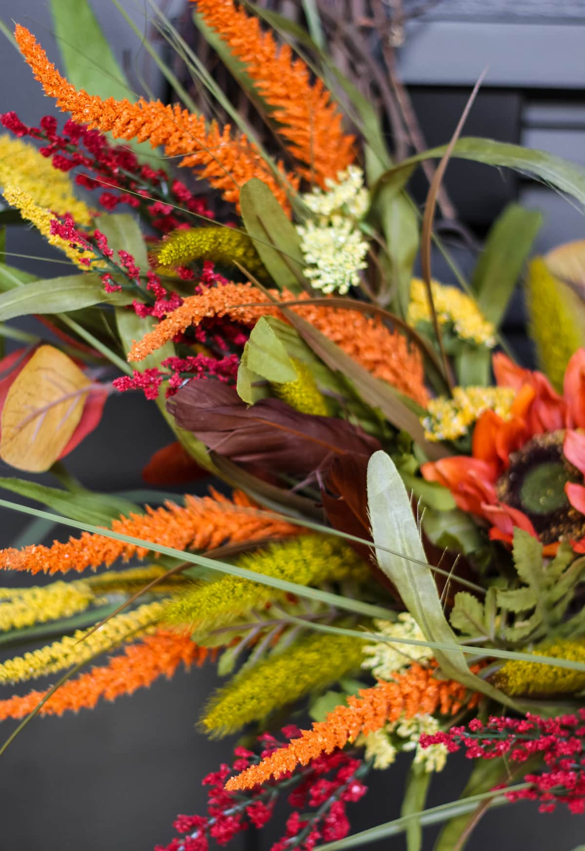 a close up of orange, yellow and red fall flowers on a wreath