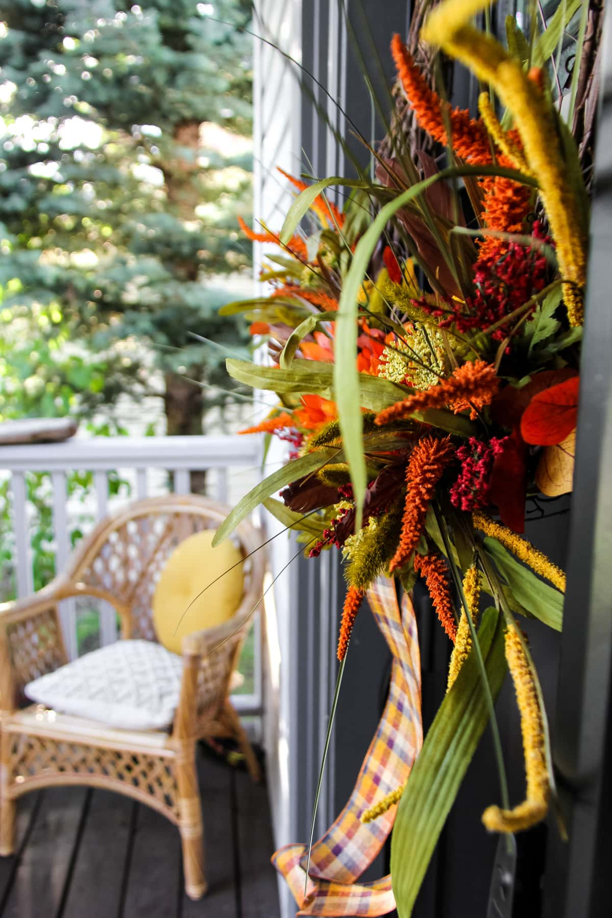 a side view of a fall wreath hanging on a black front door. in the background is a wicker chair with beige and yellow pillows