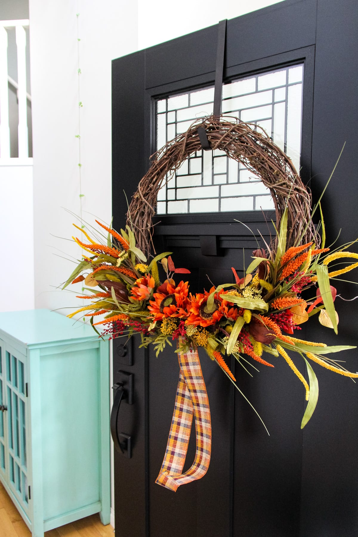 a large grapevine wreath decorated with dried fall florals stems and a plaid ribbon hangs on a black door. in the background is a teal cabinet