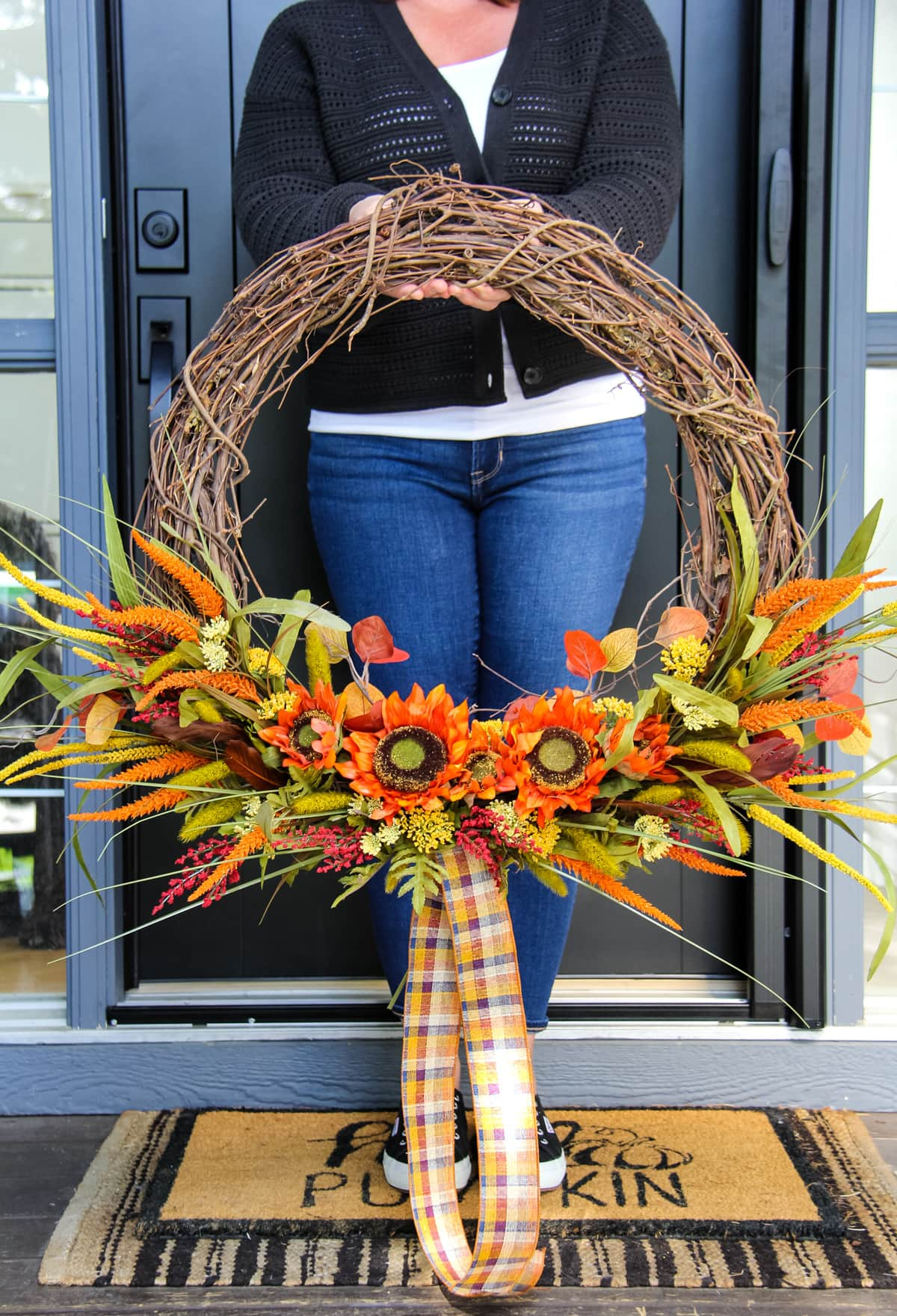 a woman stands in front of a black door holding a large grapevine wreath decorated with dried fall florals stems and a plaid ribbon