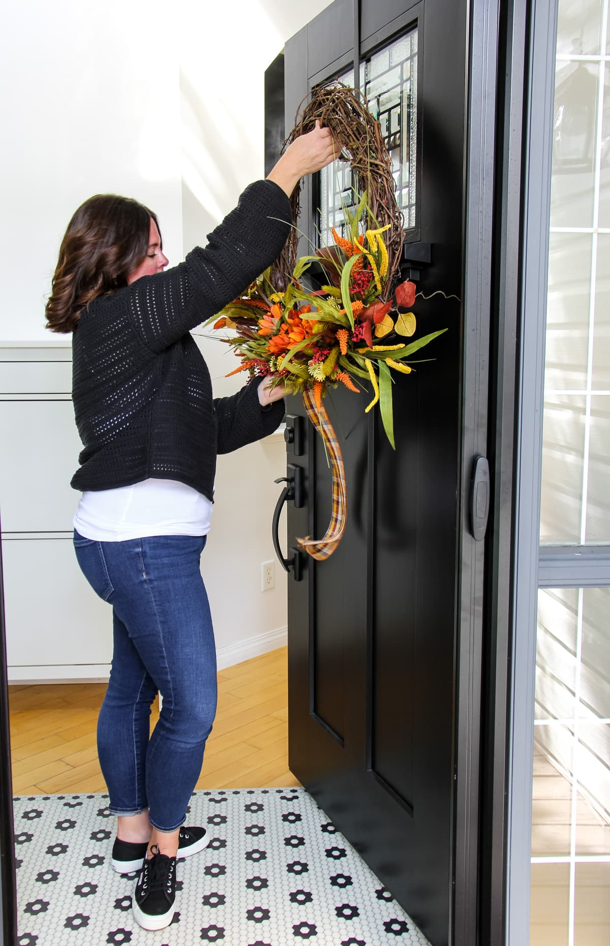 a woman is hanging a large grapevine wreath on a black door. it is decorated with dried fall florals stems and a plaid ribbon