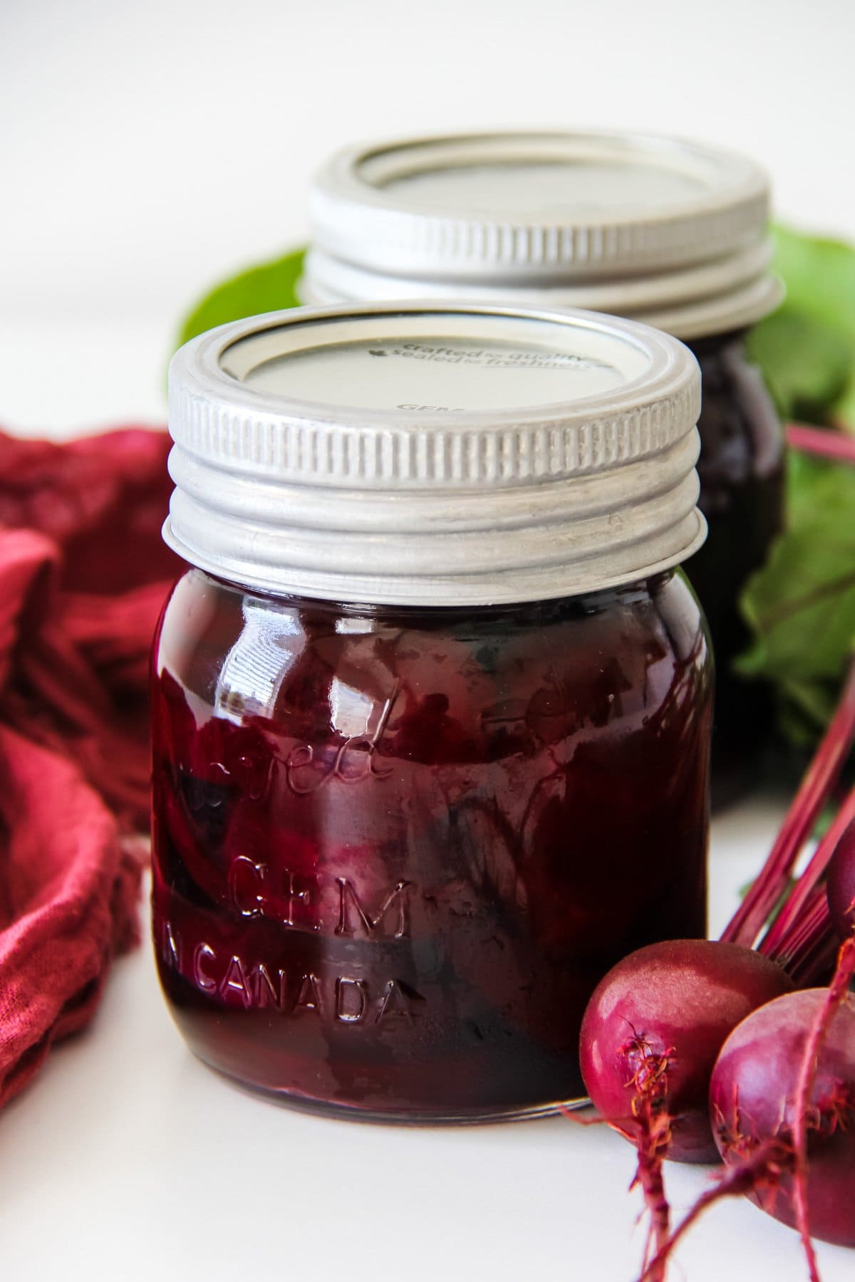 two jars of Pickled Beets. in the background are fresh beets with green leaves and a maroon coloured cloth.