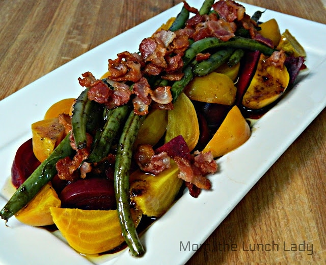 a white plate with yellow and purple roasted beets. the salad is topped with bacon and green beans