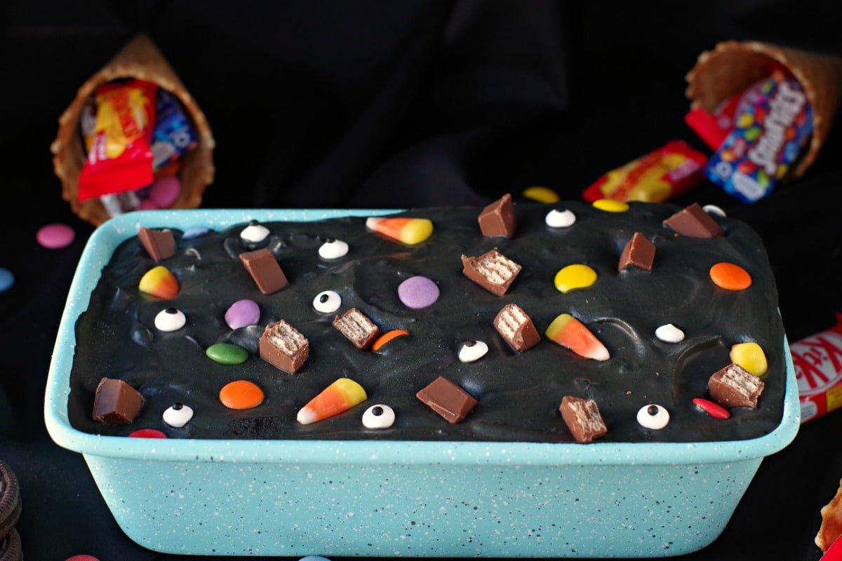 a teal coloured loaf pan filled with black ice cream and topped with colourful candy