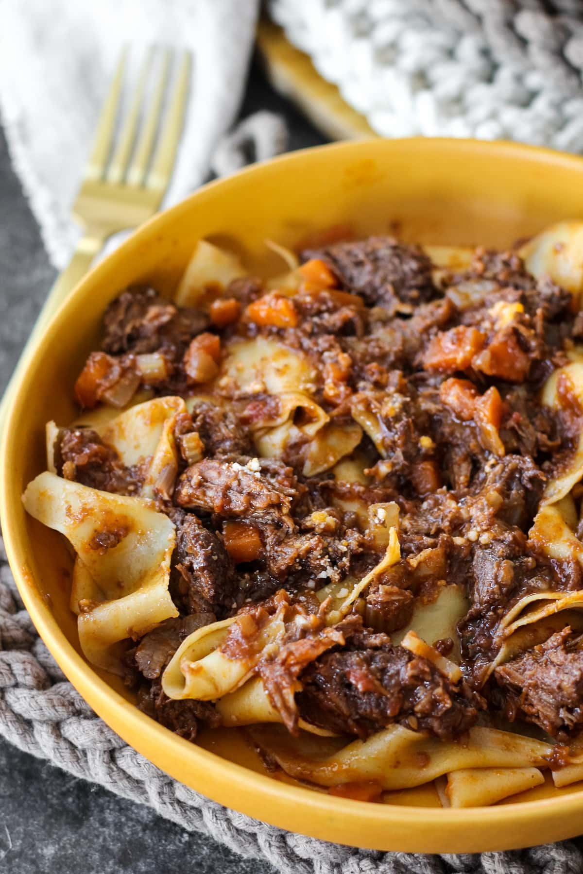 a close up view of half of a yellow bowl filled with beef ragu over pappardelle pasta
