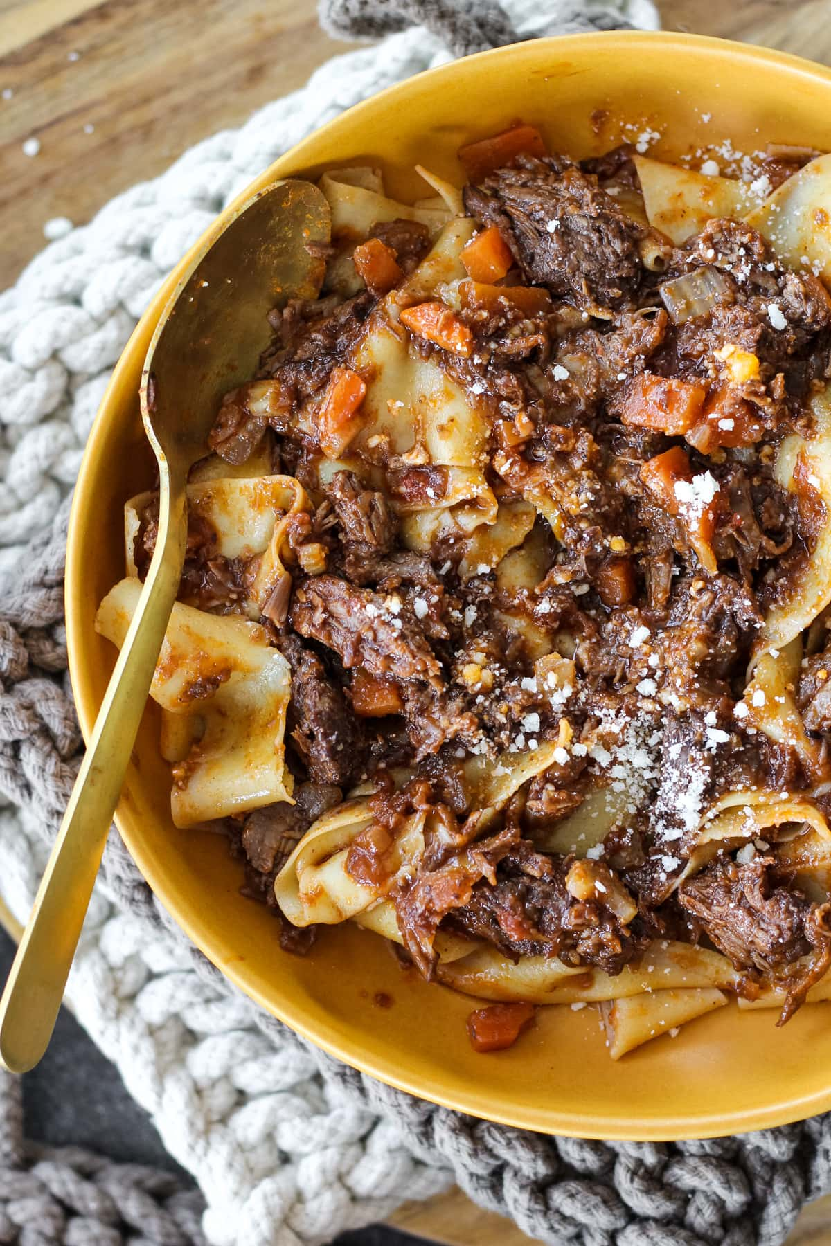 a close up top down view of half of a yellow bowl filled with beef ragu over pappardelle pasta
