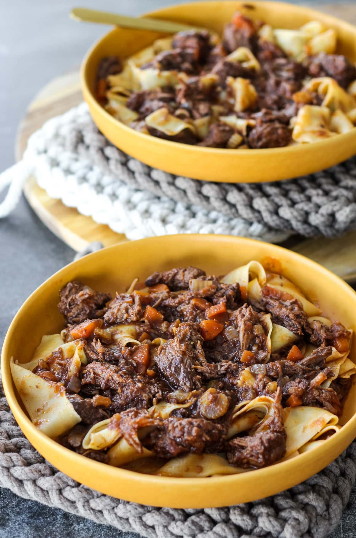 two yellow bowls sitting on knitted pot holders. the bowls are full of beef ragu over pappardelle pasta
