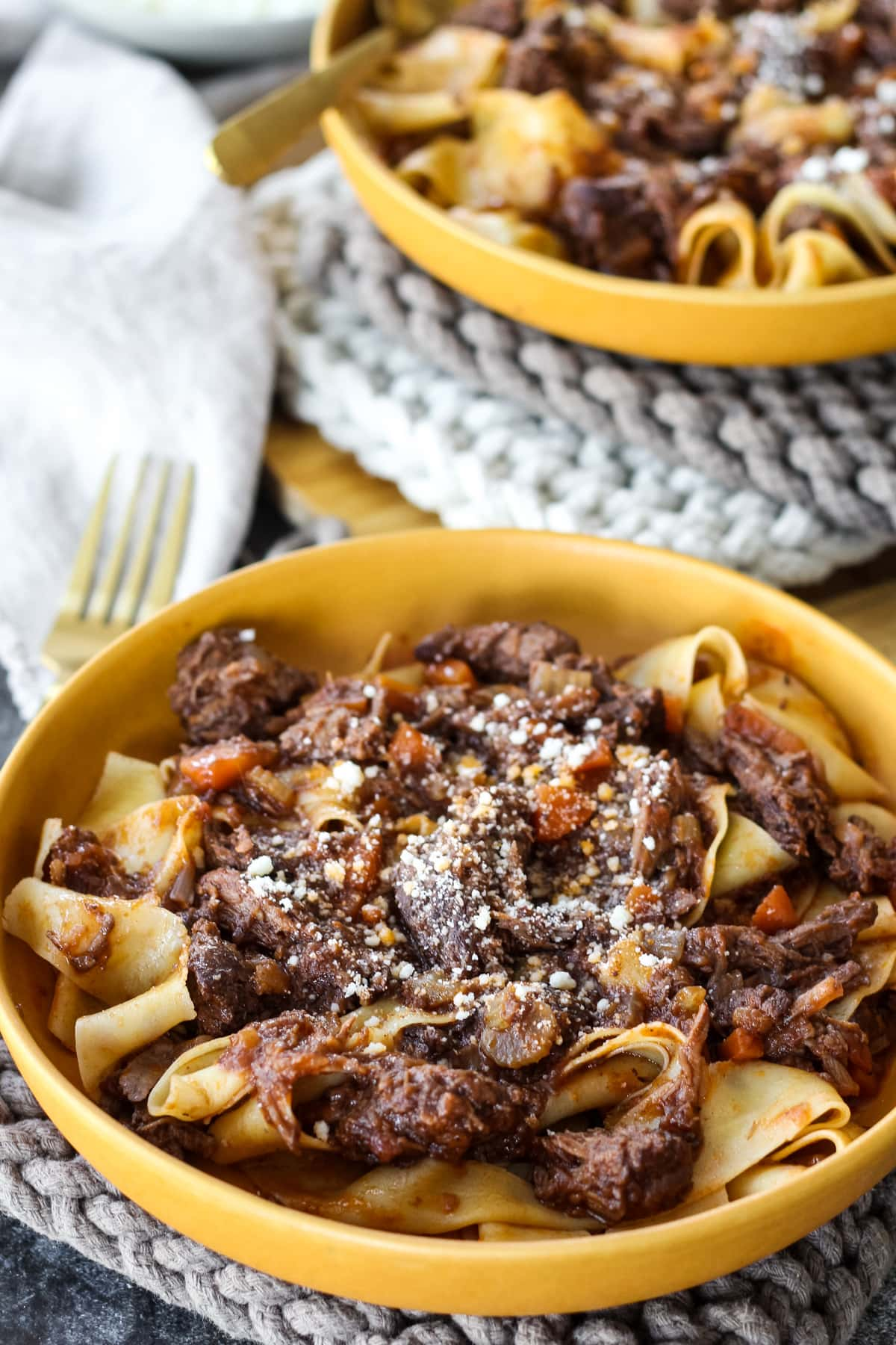 a close view of a yellow bowl filled with beef ragu over pappardelle pasta