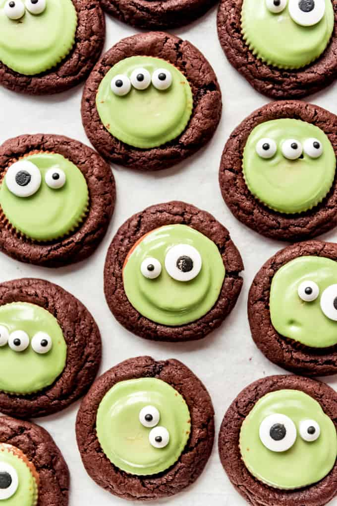 a top down view of chocolate cookies with green candy circles in the centre. on each of the green candies are two eyeballs