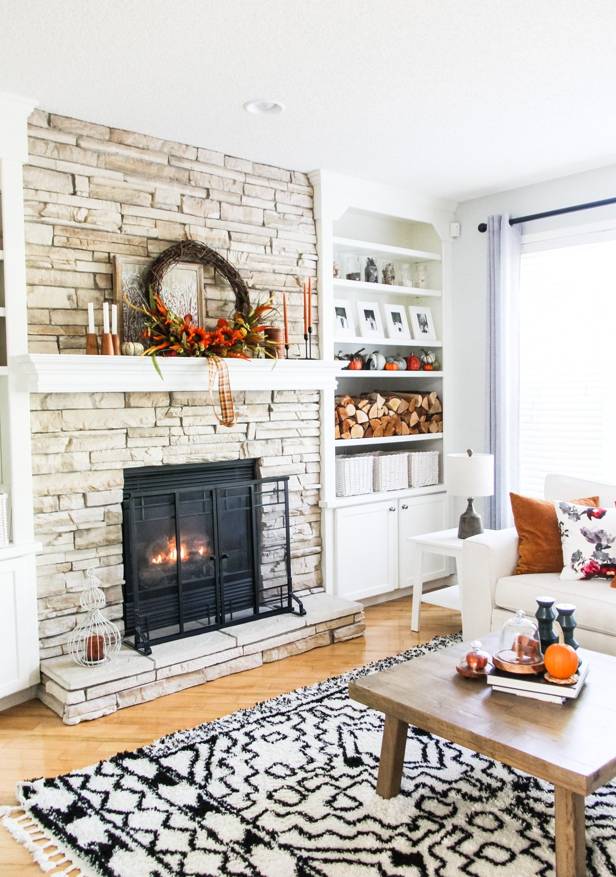 Fall Home Tour: A Simple Fall Mantel on a stone fireplace that is decorated with a large grapevine wreath, candles, stacked wood and pumpkins. In the foreground is a black and white rug, a coffee table with candles and books