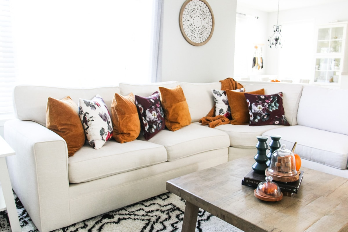 a view of a cream coloured sectional couch on a black and white rug. the couch is filled with rust and floral pillows. in the foreground is a coffee table with candles and cloches