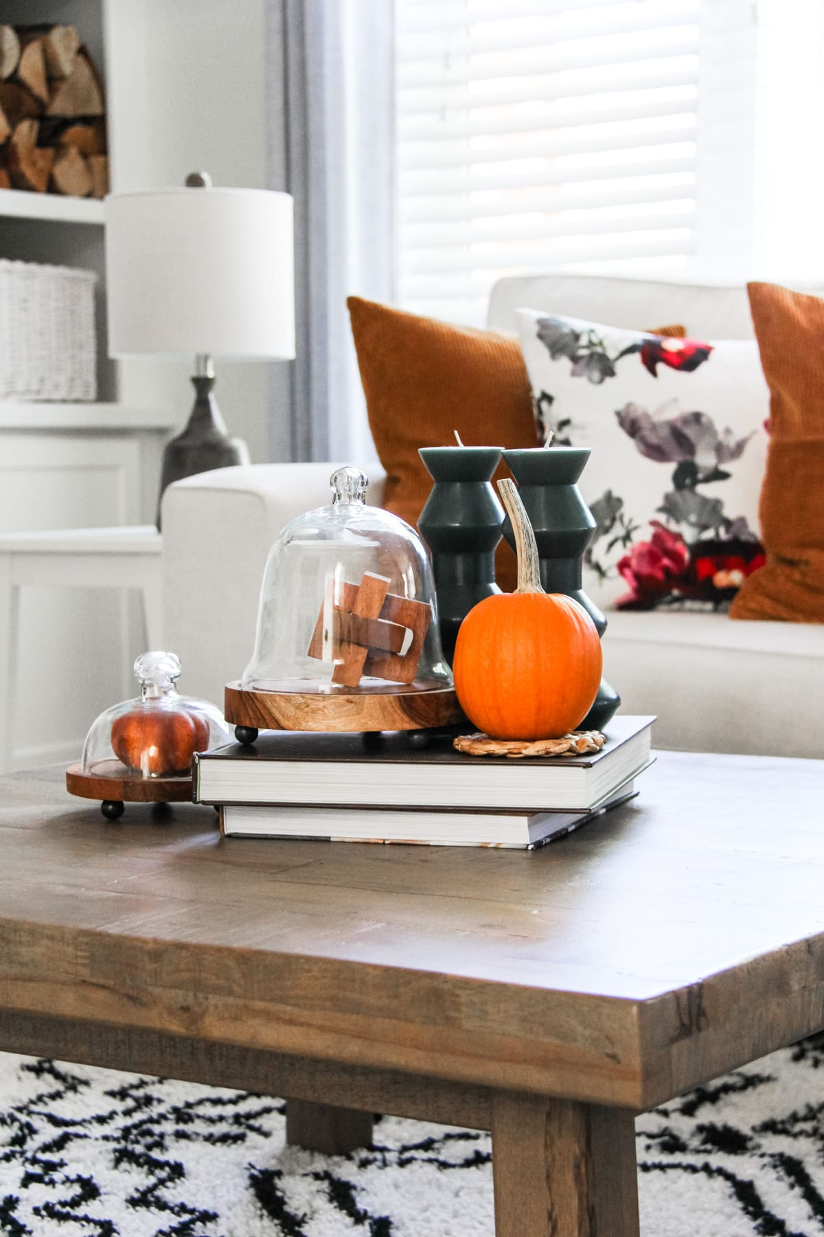 a close up of a coffee table topped with a mini orange pumpkin, blue candles, stacked books and cloches. in the background is a cream coloured couch with rust and floral pillows