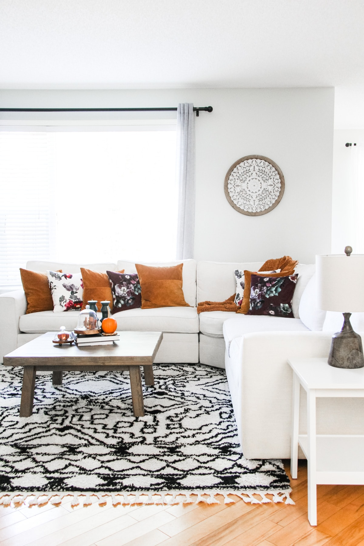 Fall Home Tour: a view of a cream coloured sectional couch on a black and white rug. the couch is filled with rust and floral pillows