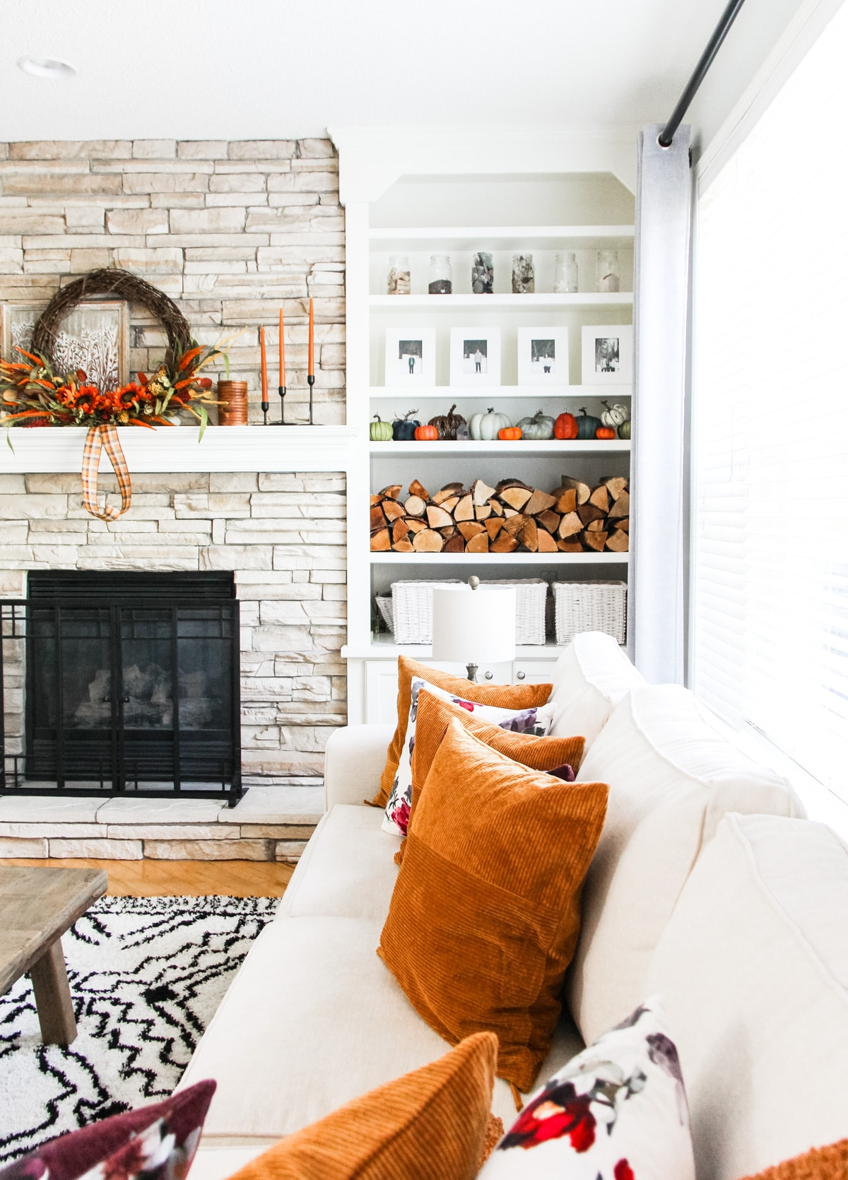 A Simple Fall Mantel on a stone fireplace that is decorated with a large grapevine wreath, candles, stacked wood and pumpkins