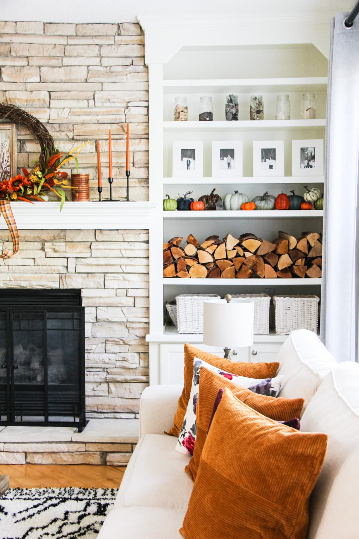 a Fall Home Tour: a set of white shelves filled with stacked wood, pictures in white frames, pumpkins, glass jars and white baskets