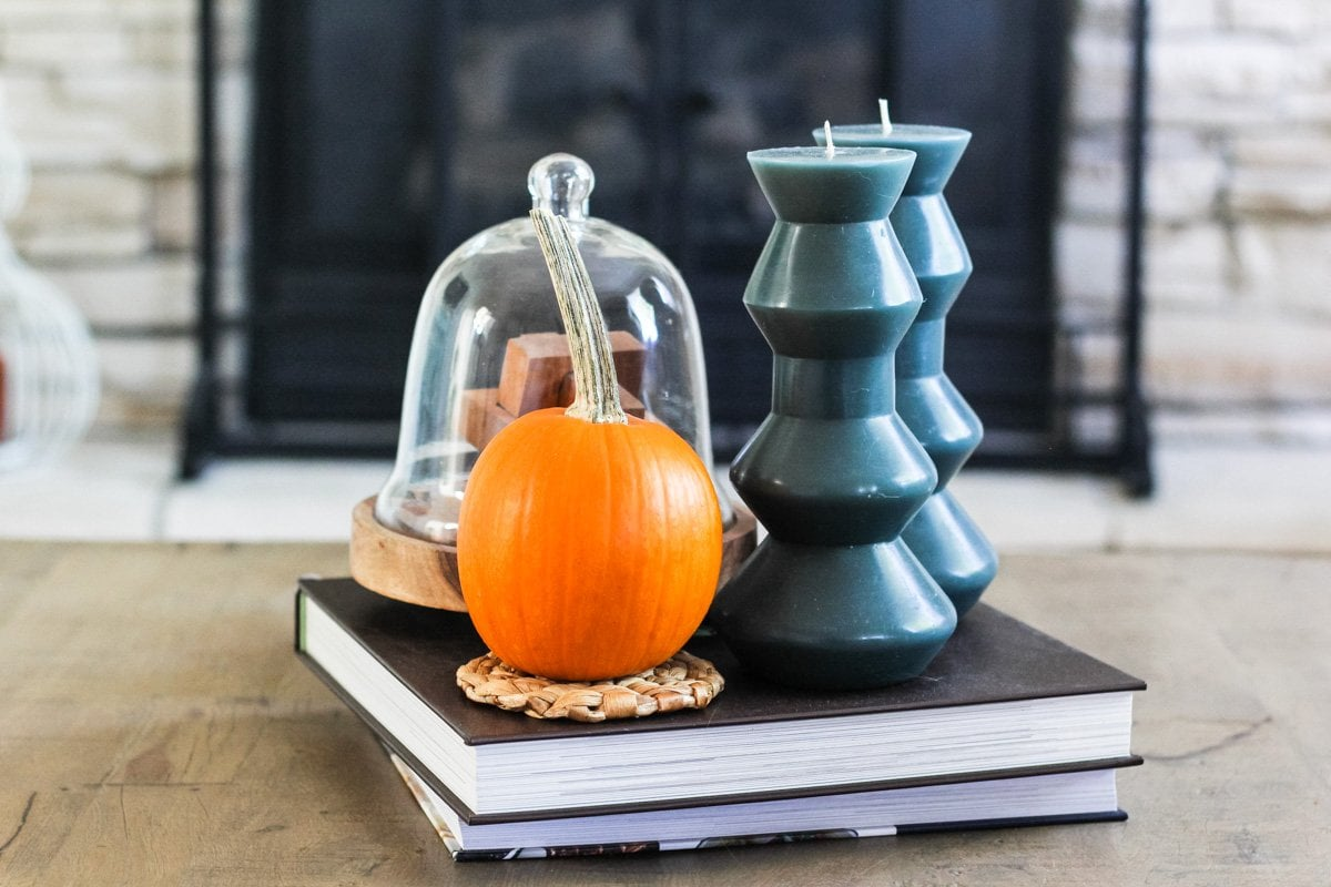 a close up of a coffee table topped with a mini orange pumpkin, blue candles, stacked books and cloches