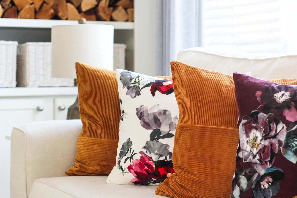 a close up of rust and floral pillows on a white couch