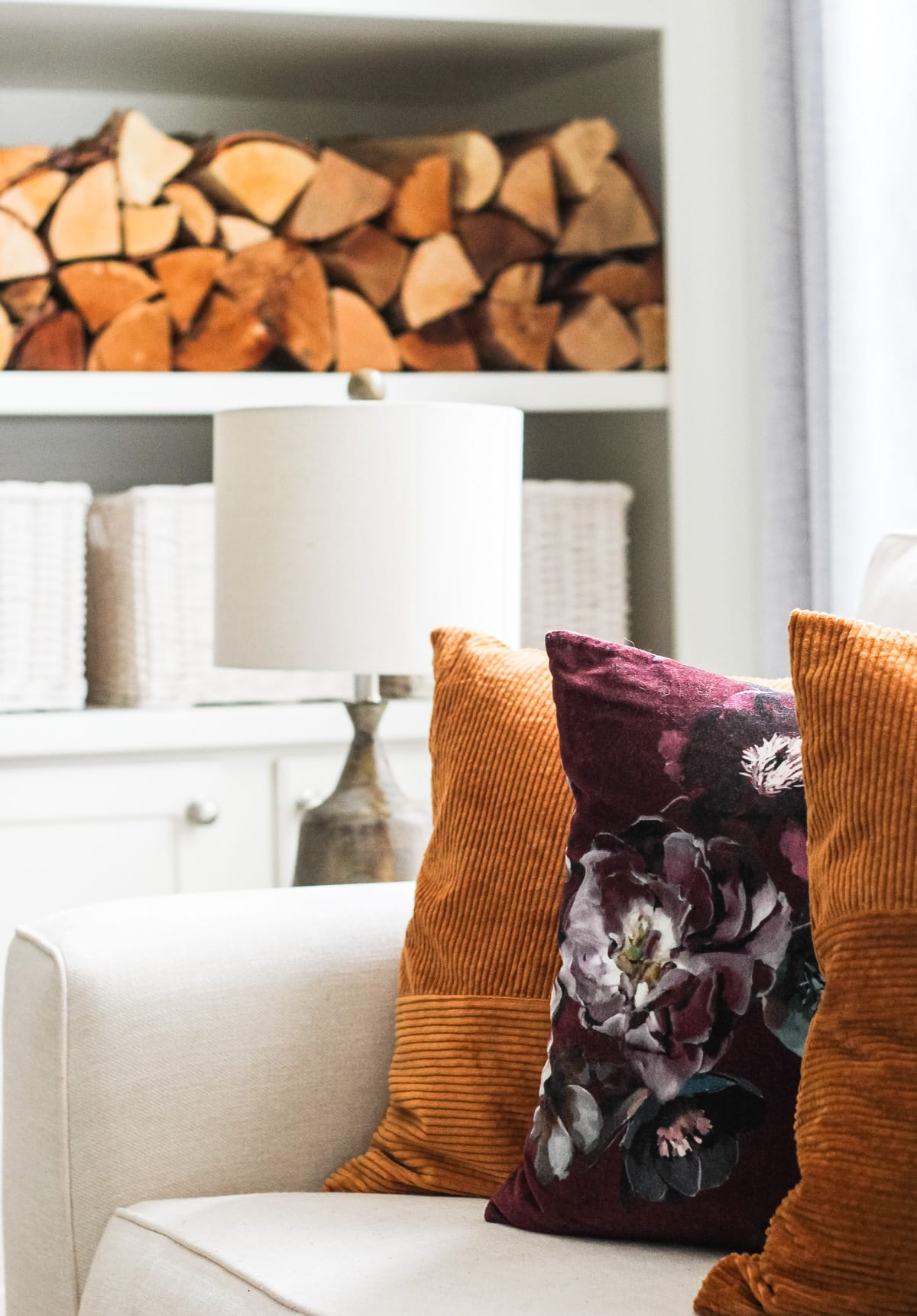 a close up of rust and floral pillows on a white couch. in the background is a lamp and a stack of wood in white shelving