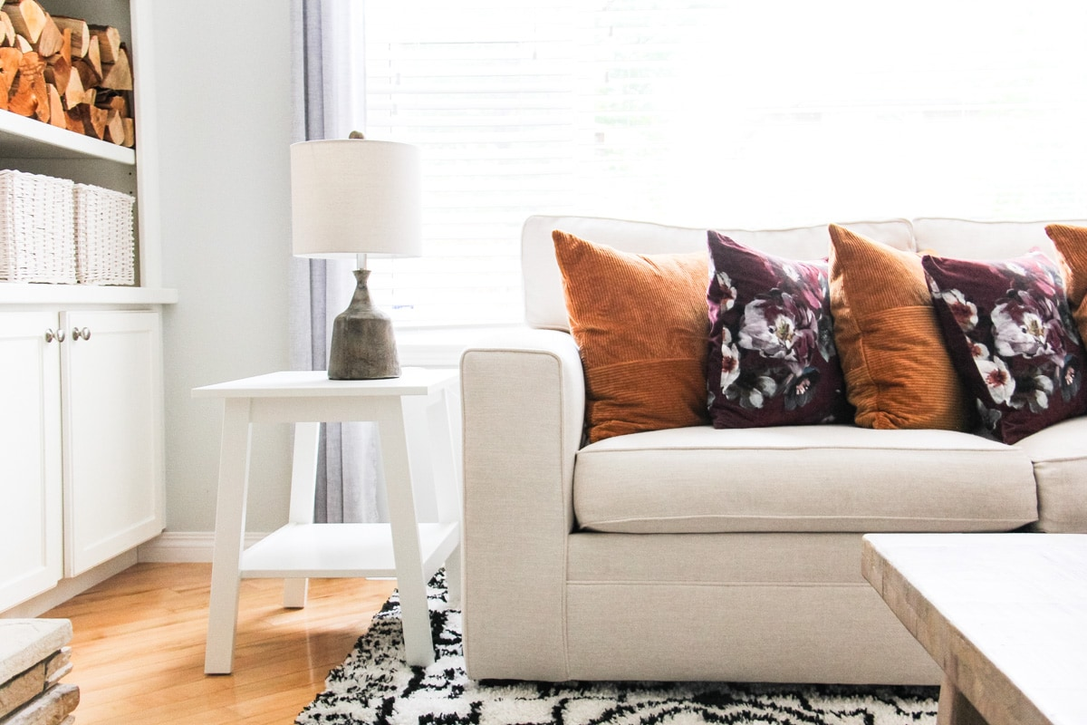 a view of a cream coloured sectional couch on a black and white rug. the couch is filled with rust and floral pillows