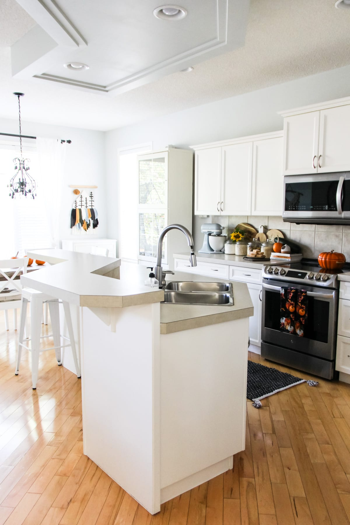 Fall Home Tour: a white kitchen and island. there is a black and steel stove. the cream coloured kitchen counters have jars of ingredients, a mixer, flowers and pumpkins