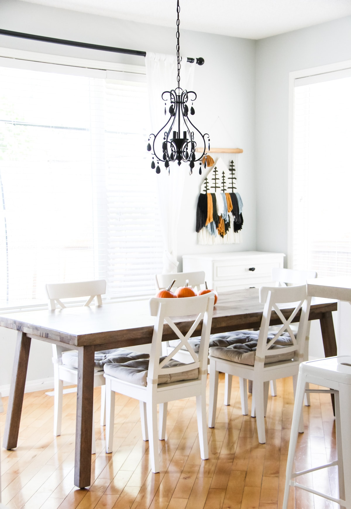 a wooden kitchen table decorated with three mini pumpkins. in the foreground is a black chandelier. in the background is a yarn wall hanging