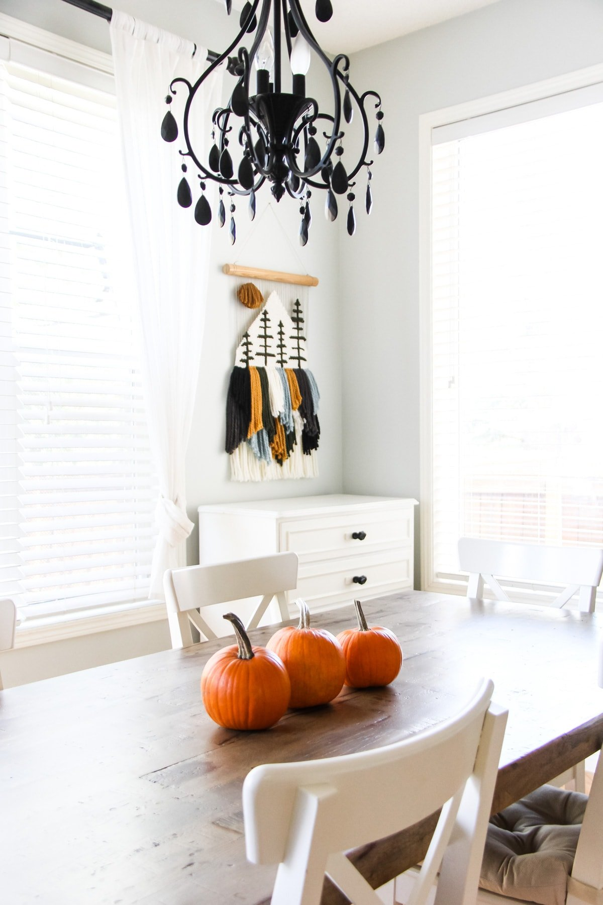 a fall home tour: a wooden kitchen table decorated with three mini pumpkins. in the foreground is a black chandelier. in the background is a yarn wall hanging