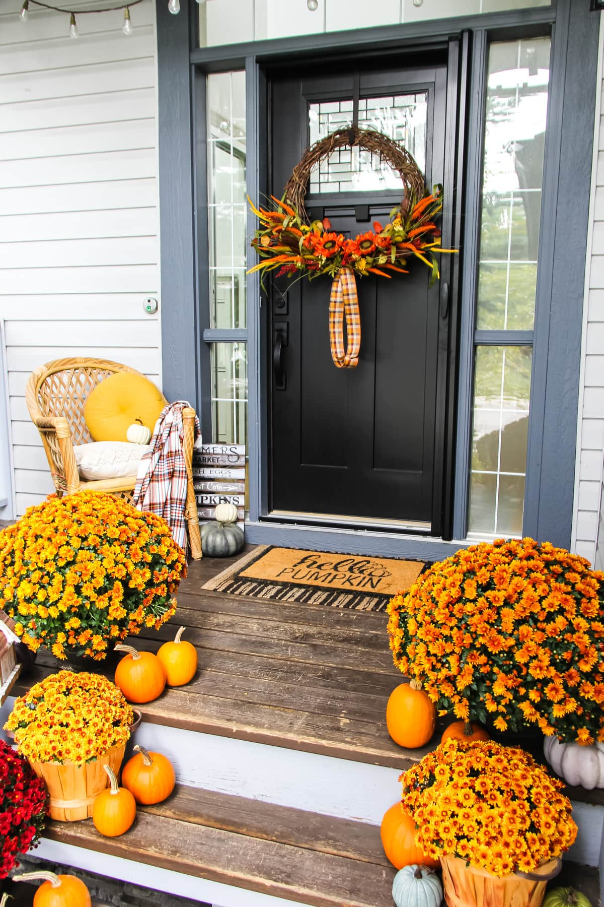 a house porch decorated with orange and red chrysanthemums, mini orange pumpkins, candles, a blue grass and a wicker chair. on the black door hangs a large grapevine wreath with fall florals.