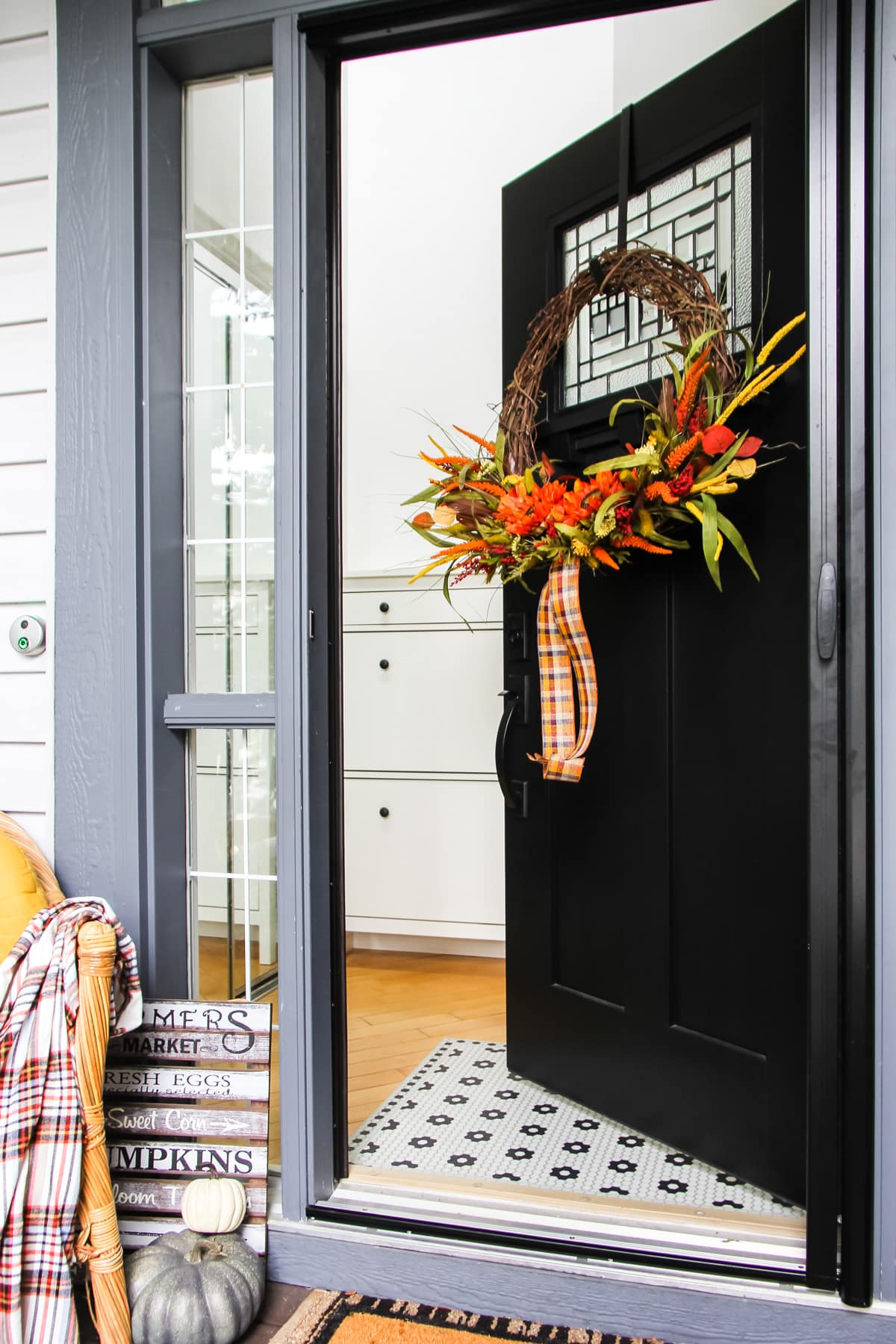 a black craftsman door has a fall wreath hung on it. the door is partially opened as a welcome into a fall home tour