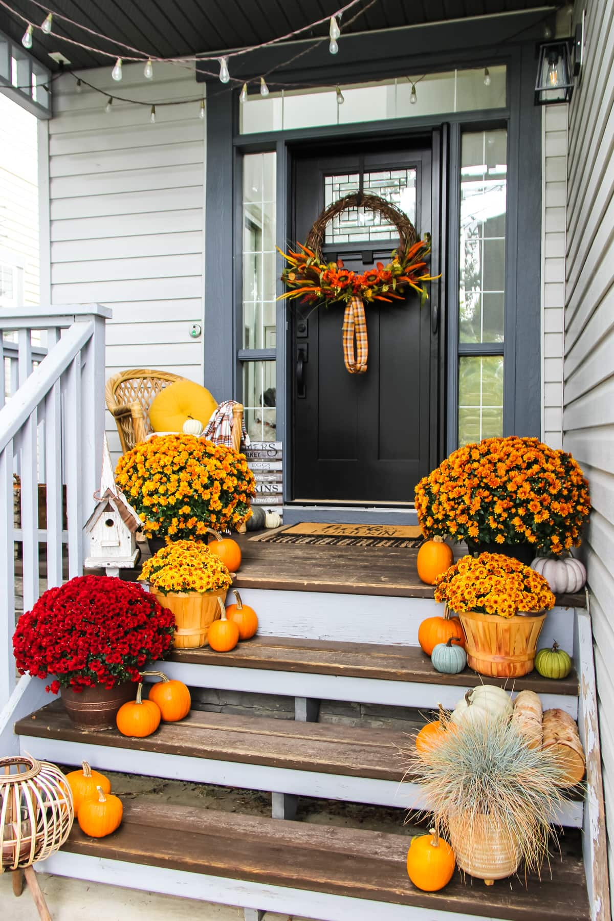 a Fall Home Tour starts on a porch filled with gold mums, pumpkins and a large fall wreath