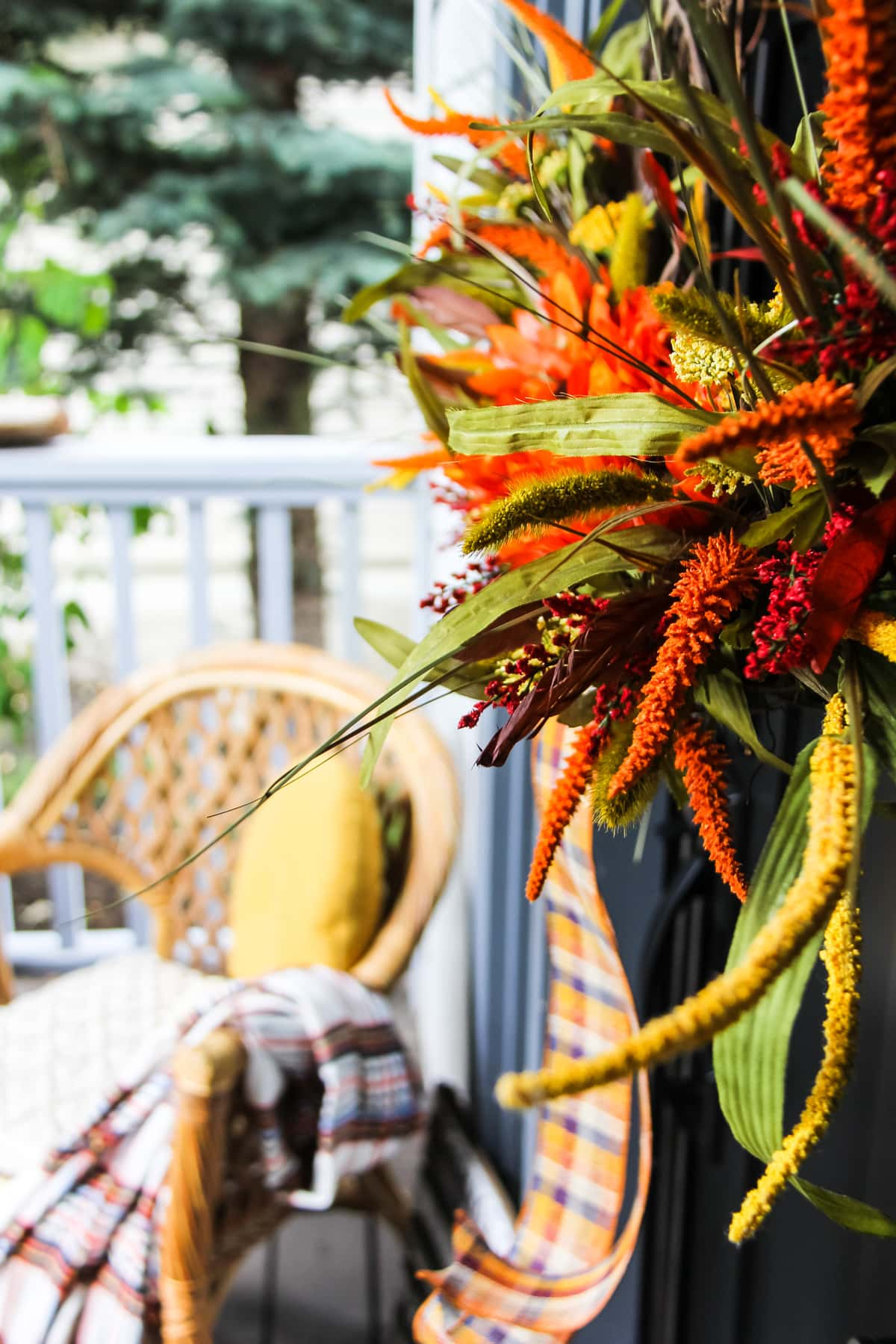a side view close up of a fall wreath. in the background is a wicker chair with a yellow pillow and plaid blanket