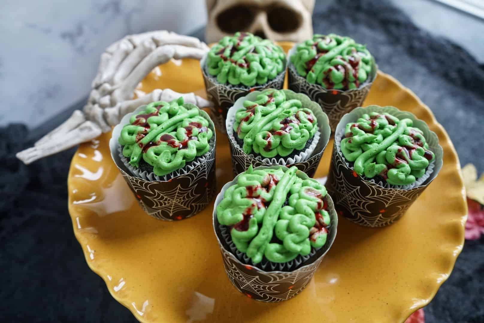 a top down view of six cupcakes with green icing in the pattern of brains. the cupcakes are sitting on a yellow plate