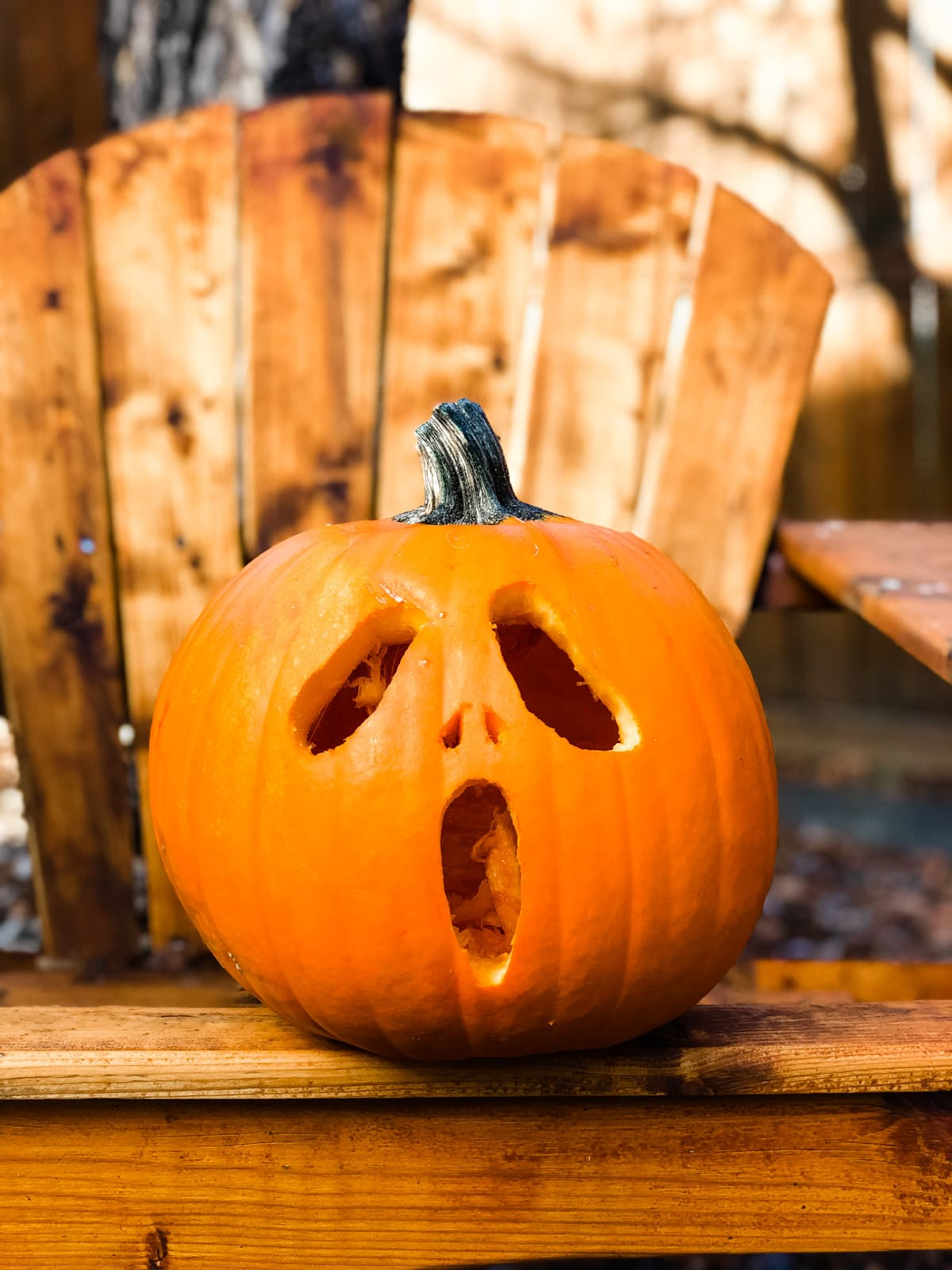an orange pumpkin withe the Scream face carved into it